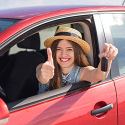 Happy Girl sitting in red card after purchasing her new car with an auto loan